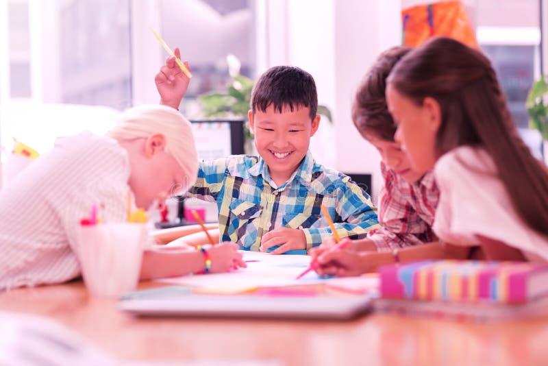 Lächelnder Junge, der unter seinen zeichnenden Freunden sitzt stockfoto