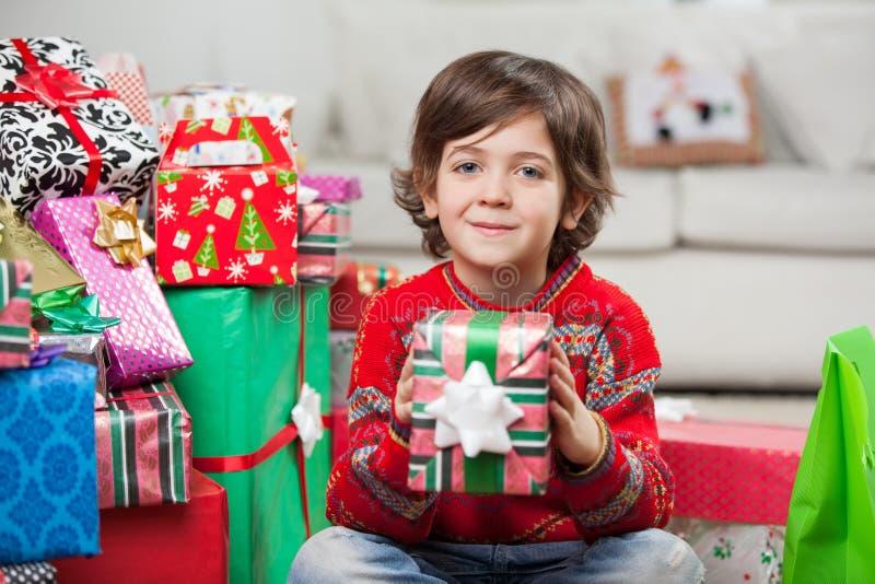 Lächelnder Junge, der zu Hause Weihnachtsgeschenk hält lizenzfreie stockfotografie