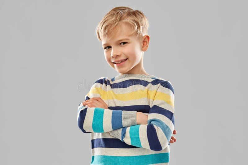Lächelnder Junge in gestreiftem Pullover mit den gekreuzten Armen lizenzfreies stockfoto