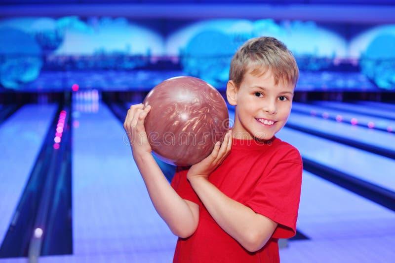 Lächelnder Junge hält Kugel im Bowlingspielklumpen an lizenzfreies stockfoto