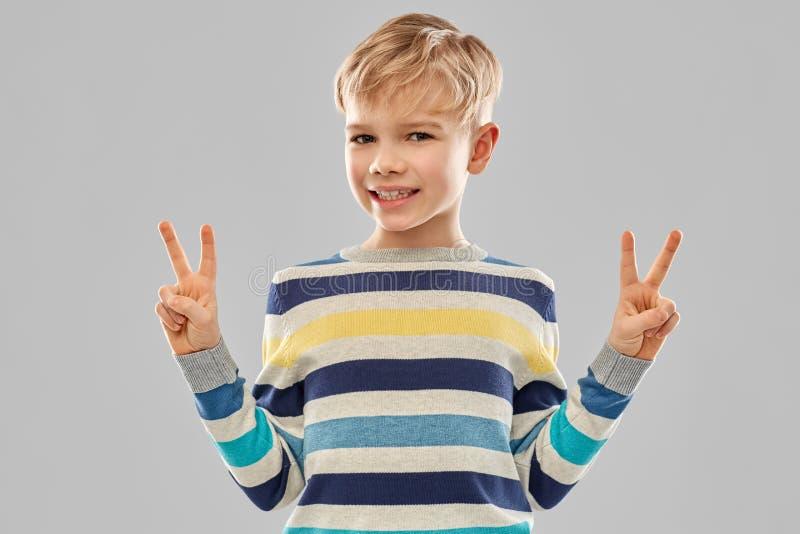 Lächelnder Junge im gestreiften Pullover, der Frieden zeigt lizenzfreie stockfotos