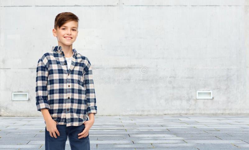 Lächelnder Junge im karierten Hemd und in den Jeans lizenzfreies stockfoto