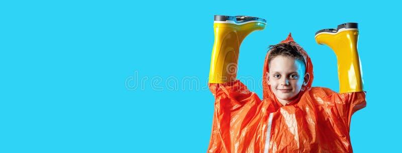 Lächelnder Junge im orange Regenmantel haftete seine Hände in den Gummistiefeln auf blauem Hintergrund lizenzfreie stockfotos