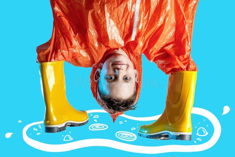 Lächelnder Junge im orange Regenmantel haftete seine Hände in den Gummistiefeln auf blauem Hintergrund stockbilder