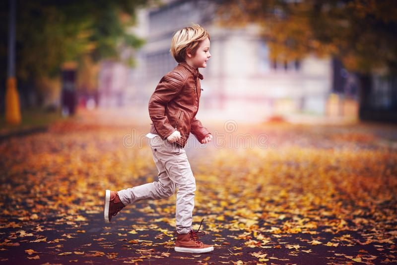 Lächelnder Junge, Kind, das Spaß im Herbststadtpark unter gefallenen Blättern hat lizenzfreie stockfotos