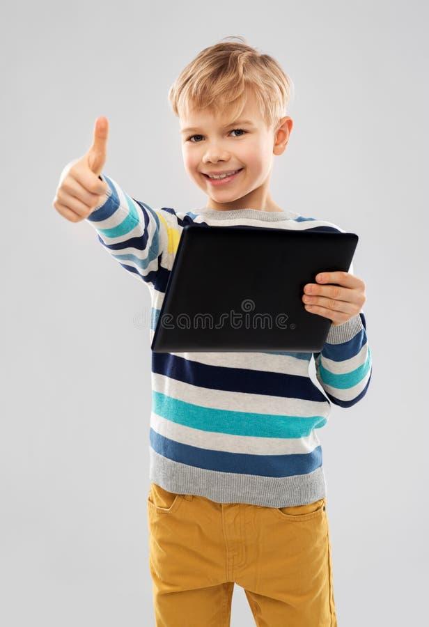 Lächelnder Junge mit dem Tablet-Computer, der sich Daumen zeigt lizenzfreies stockbild