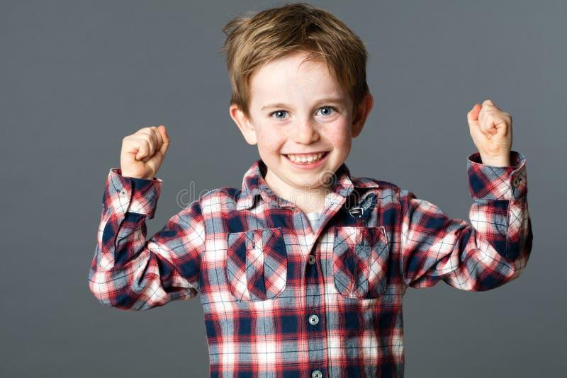 Lächelnder Junge mit den Sommersprossen, die starke Fäuste für starke Gesundheit anheben lizenzfreie stockfotos
