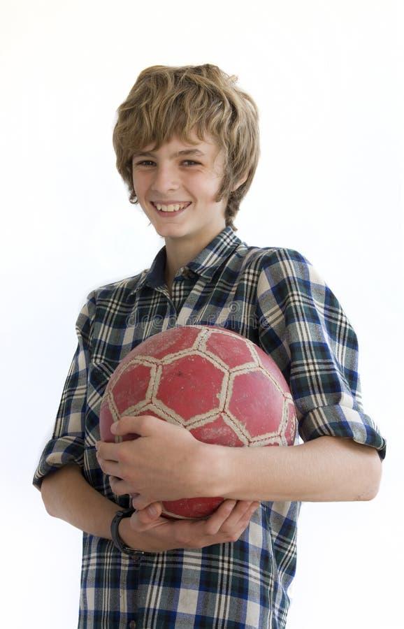 Lächelnder Junge mit einer alten Fußballkugel stockfoto