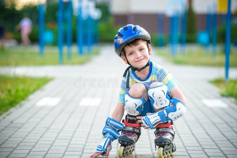Lächelnder Junge mit Inline-Rochen und Schutzausrüstung lizenzfreies stockfoto