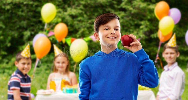 Lächelnder Junge mit rotem Apfel an der Geburtstagsfeier stockfotos