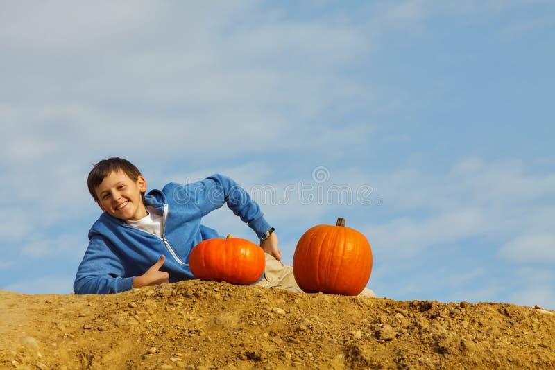 Lächelnder Junge mit zwei Kürbisen lizenzfreie stockbilder