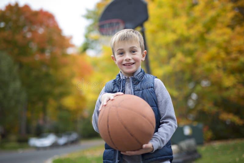 Lächelnder Junge sechs Jahre alt mit einem Korbball stockfotos