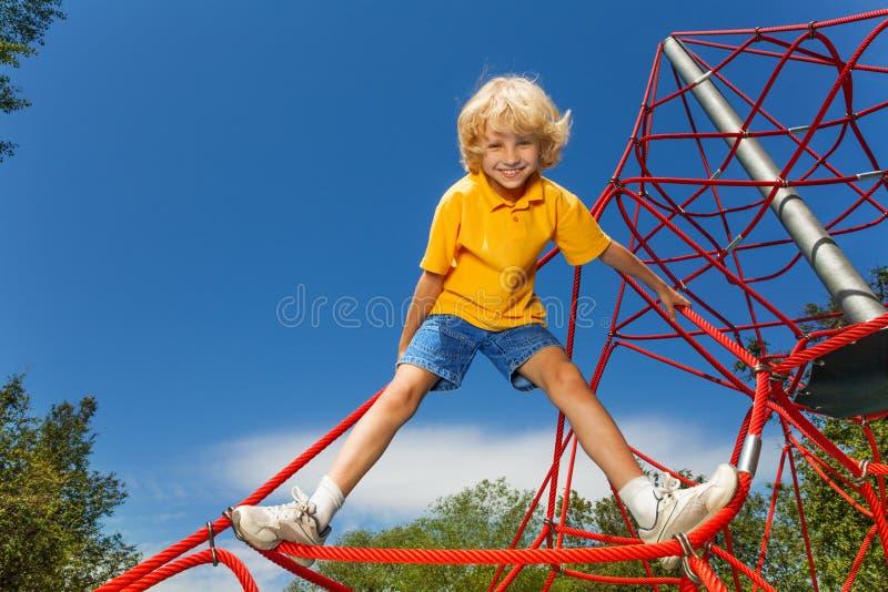 Lächelnder Junge steht auf rotem Seil mit den Beinen auseinander lizenzfreies stockfoto