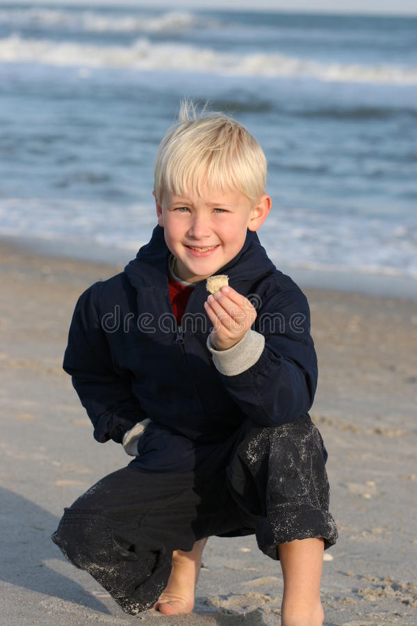 Lächelnder Junge am Strand zeigt Shell lizenzfreie stockfotos