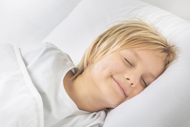 Lächelnder Jungenschlaf im Bett lizenzfreie stockfotos