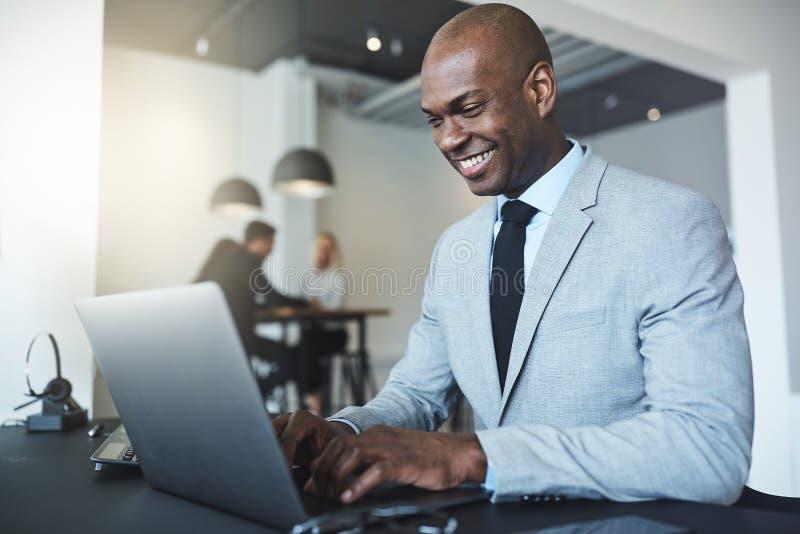 Lächelnder junger Afroamerikanergeschäftsmann, der an einem Laptop arbeitet stockbild