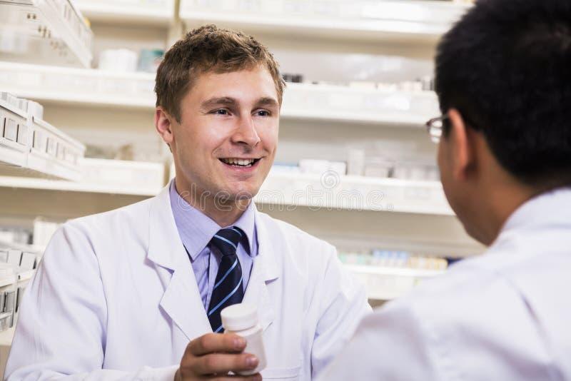 Lächelnder junger Apotheker, der einem Kunden rezeptpflichtiges Medikament zeigt lizenzfreie stockfotografie