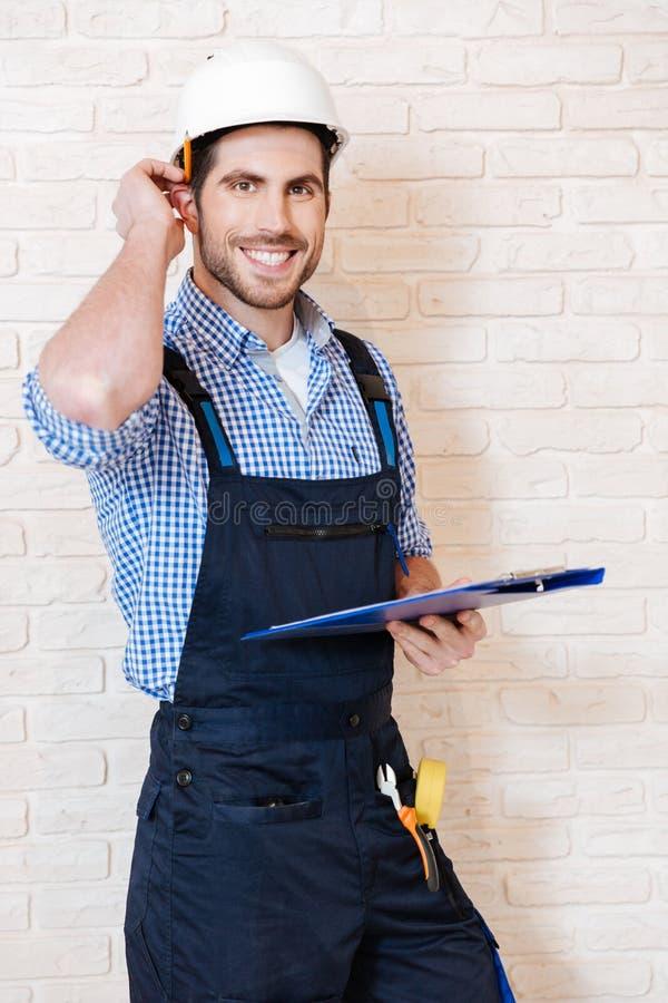 Lächelnder junger Arbeitnehmer, der Kenntnisse über sein Klemmbrett nimmt stockbilder