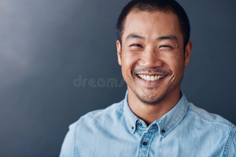 Lächelnder junger asiatischer Designer, der in einem Büro steht lizenzfreie stockfotos