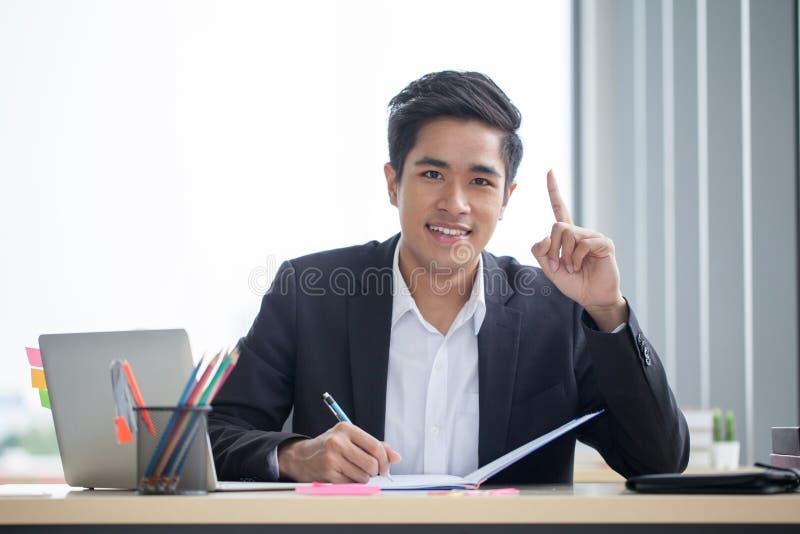 Lächelnder junger asiatischer Geschäftsmann, der mit Anmerkungsbuch auf dem Schreibtisch und Finger zeigen oben in ein modernes B lizenzfreies stockfoto