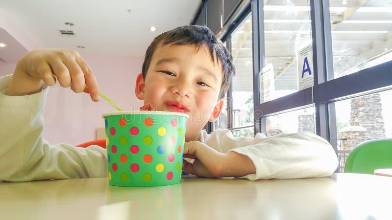 Lächelnder junger chinesischer und kaukasischer Junge, der gefrorenen Jogurt essend genießt lizenzfreies stockbild