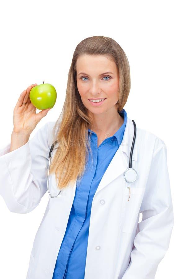 Lächelnder junger Doktor, der einen grünen Apfel gibt. stockbilder