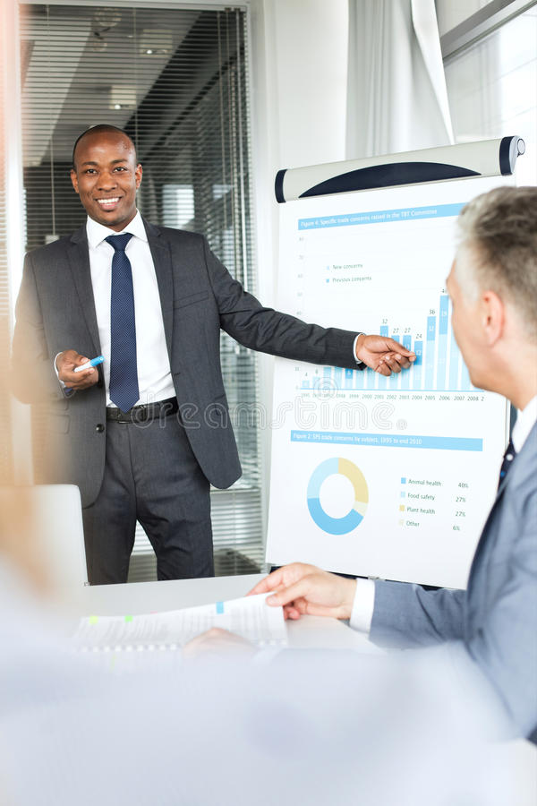 Lächelnder junger Geschäftsmann, der Darstellung in der Chefetage gibt stockbild
