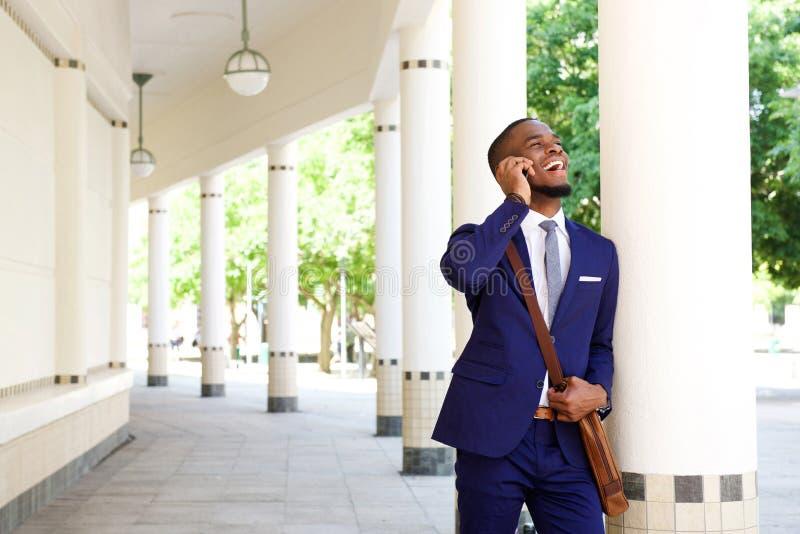 Lächelnder junger Geschäftsmann, der durch Handy nennt stockfotografie