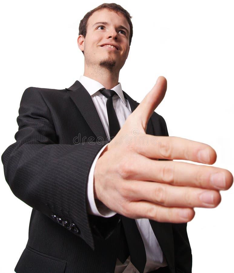 Lächelnder junger Geschäftsmann, der Hand für Händedruck gibt stockfotografie