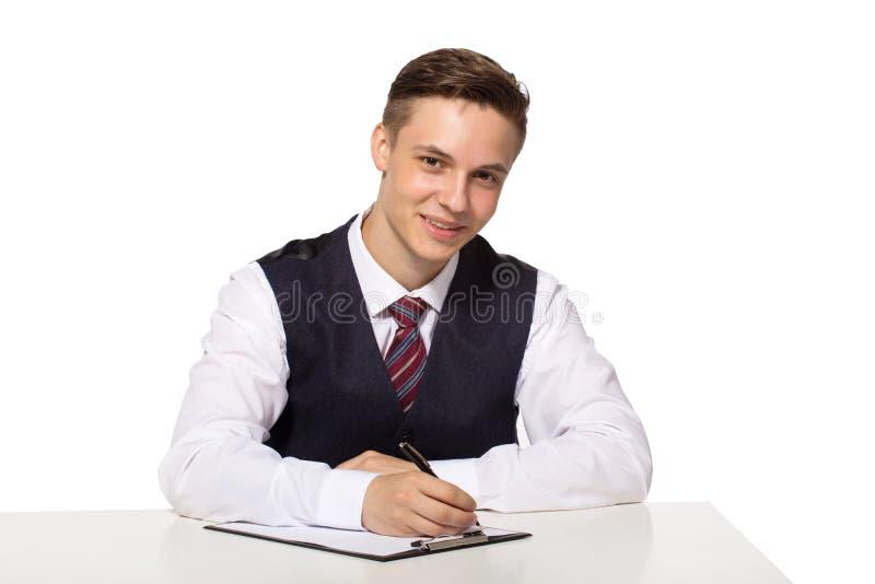 Lächelnder junger Geschäftsmann, der im Büro, sitzend am Schreibtisch arbeitet und schreiben Anmerkungen zum Klemmbrett lizenzfreie stockbilder
