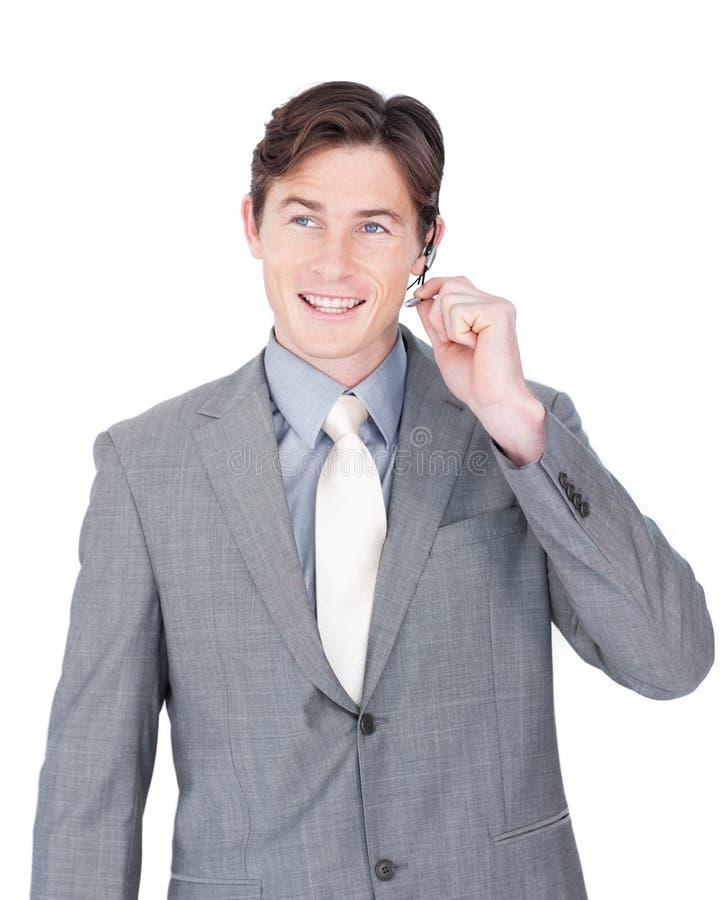 Lächelnder junger Geschäftsmann unter Verwendung des Kopfhörers stockbild