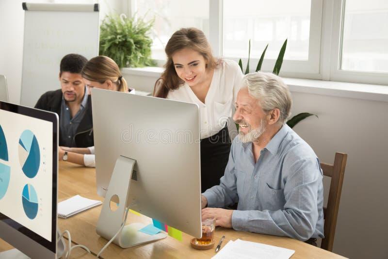 Lächelnder junger Manager, welche älterer Arbeitskraft mit Computerbüro hilft lizenzfreie stockfotos