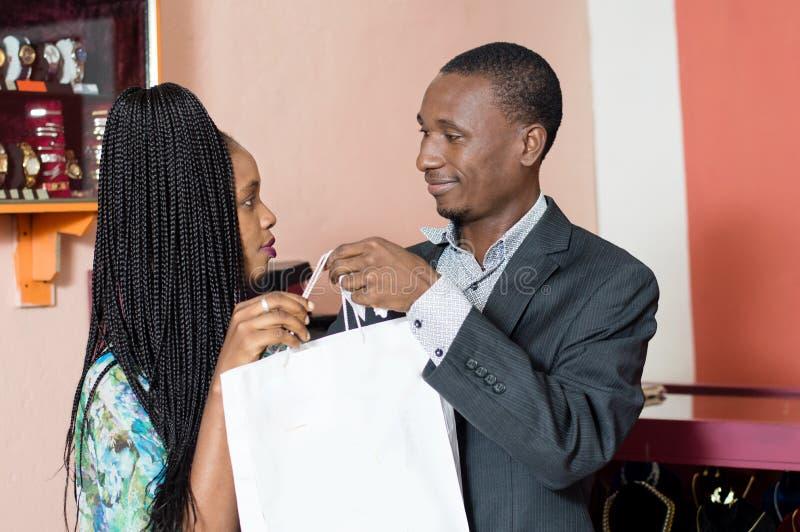 Lächelnder junger Mann bietet eine Einkaufstasche seiner Frau an stockbilder
