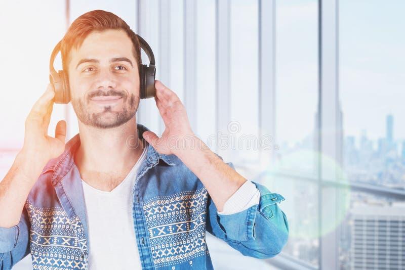 L?chelnder junger Mann in den Kopfh?rern, panoramischer Raum stockfotografie