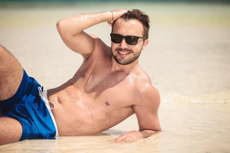 Lächelnder junger Mann, der auf dem Strand liegt stockbild
