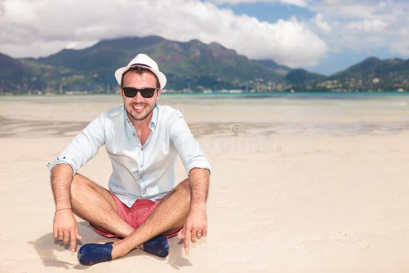 Lächelnder junger Mann, der auf dem Strand sitzt lizenzfreie stockfotos