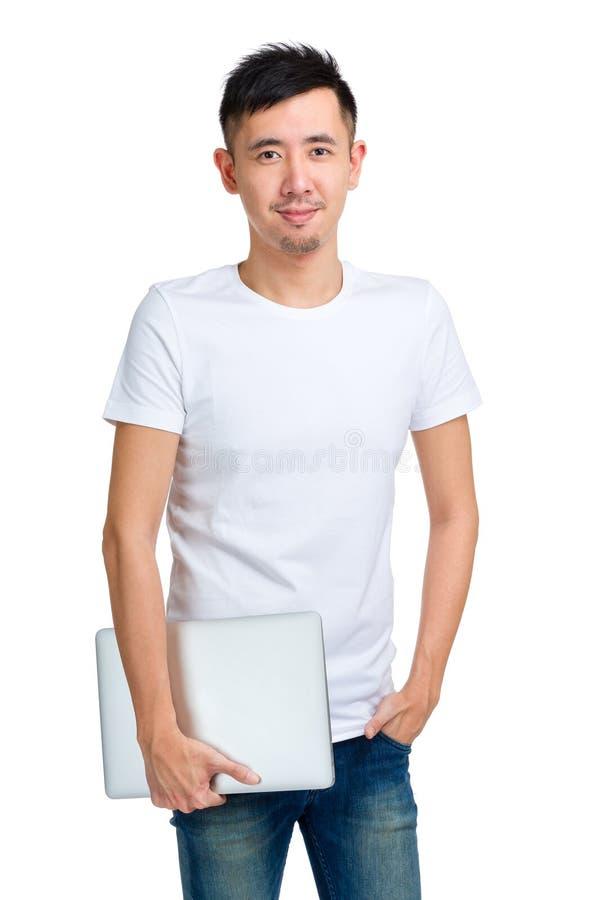 Lächelnder junger Mann, der Computer hält lizenzfreie stockbilder