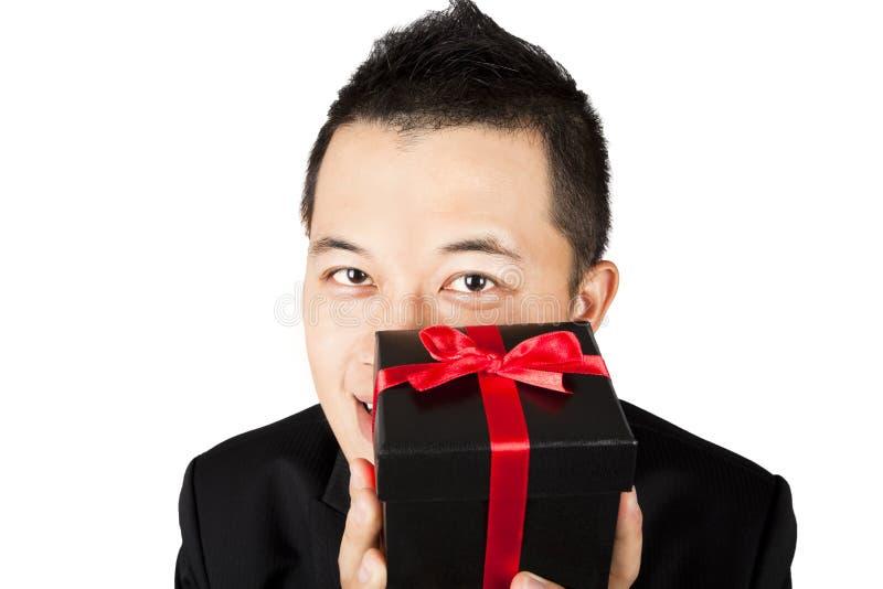 Lächelnder junger Mann, der ein Geschenk anbietet stockbild