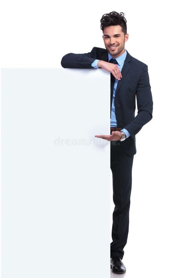Lächelnder junger Mann, der eine große leere Anschlagtafel darstellt stockfotos