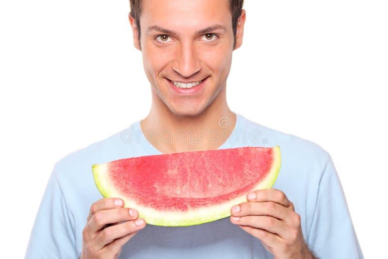 Lächelnder junger Mann, der eine Scheibe der Wassermelone anhält lizenzfreies stockbild