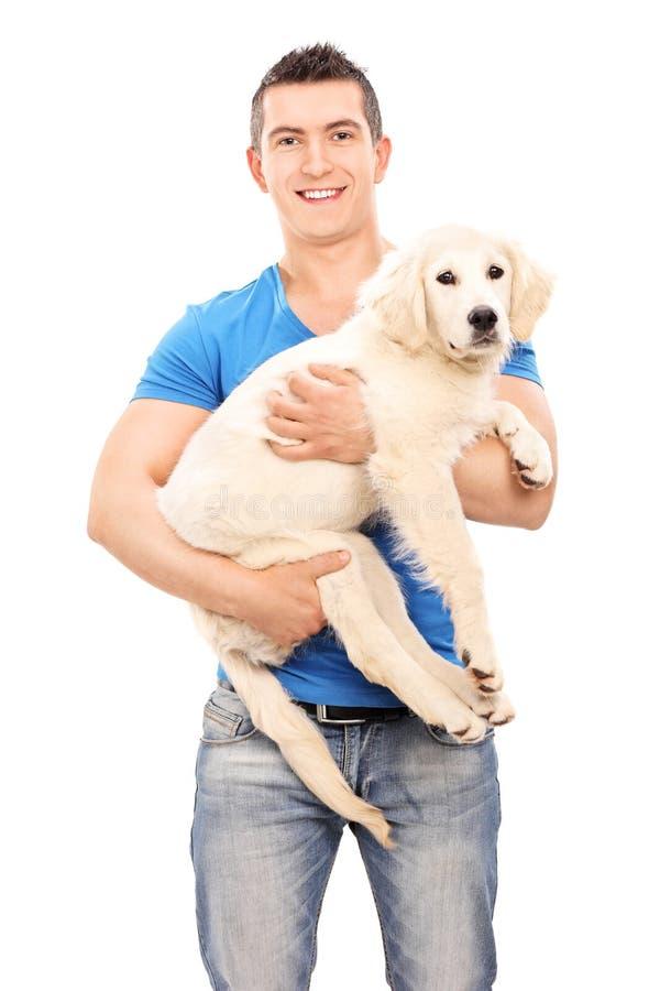 Lächelnder junger Mann, der einen Hund hält stockbild