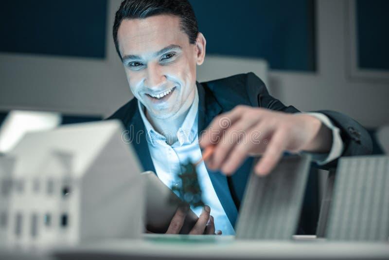 Lächelnder junger Mann, der erfolgreich sein Projekt beendet lizenzfreie stockbilder