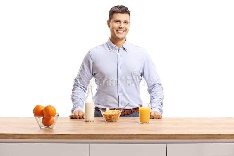 Lächelnder junger Mann, der Frühstück zubereitet lizenzfreies stockbild