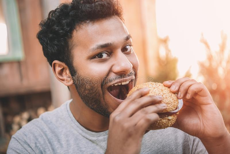 Lächelnder junger Mann, der frischen Hamburger und das Schauen beißt stockfotografie