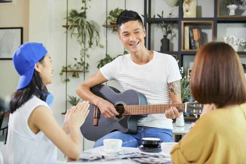 Lächelnder junger Mann, der Gitarre für Freunde spielt stockfotografie