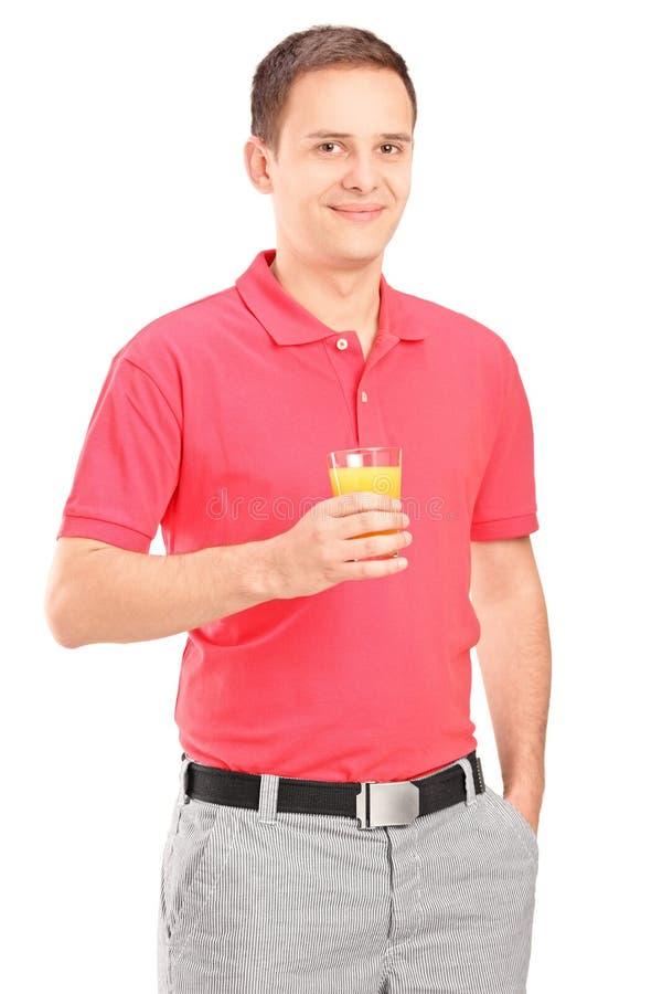 Lächelnder junger Mann, der mit einem Glas Orangensaft aufwirft lizenzfreies stockfoto