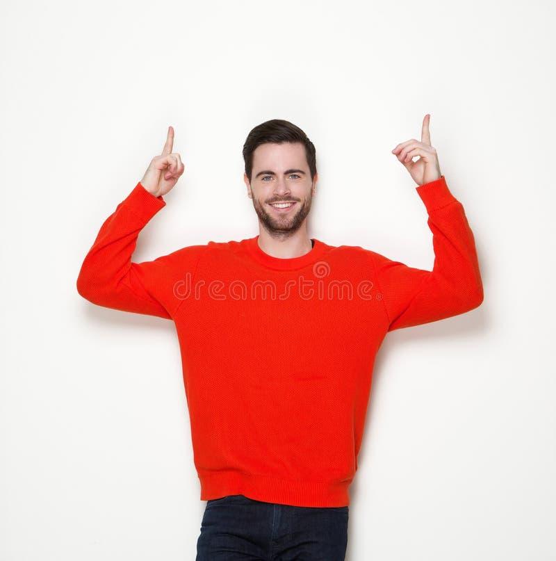 Lächelnder junger Mann, der oben Finger zeigt stockfotos