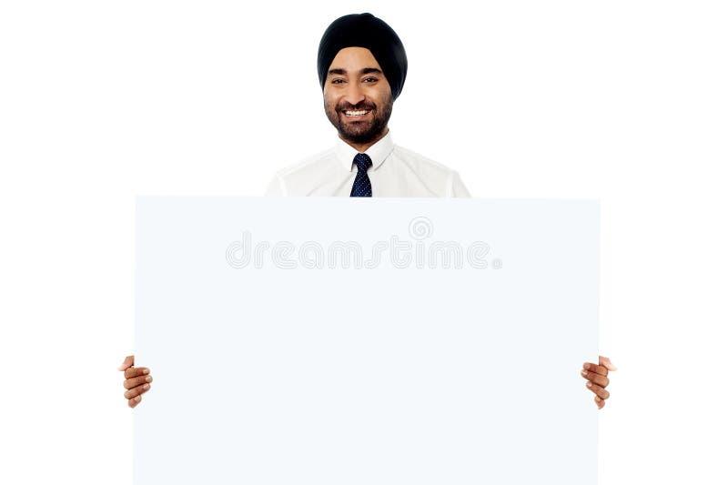 Lächelnder junger Mann, der weißes Zeichenbrett hält stockbild