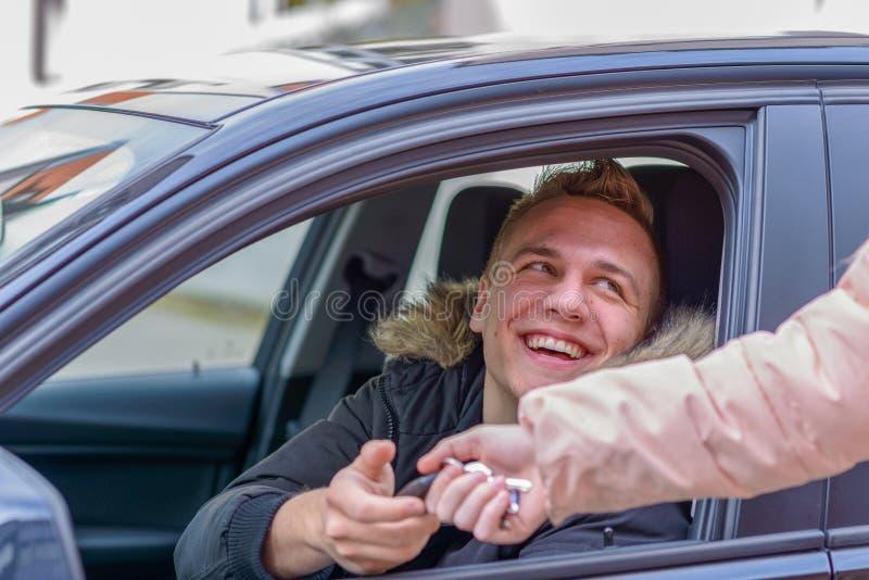 Lächelnder junger Mann in einem Auto, das seine Schlüssel übernimmt lizenzfreie stockfotos