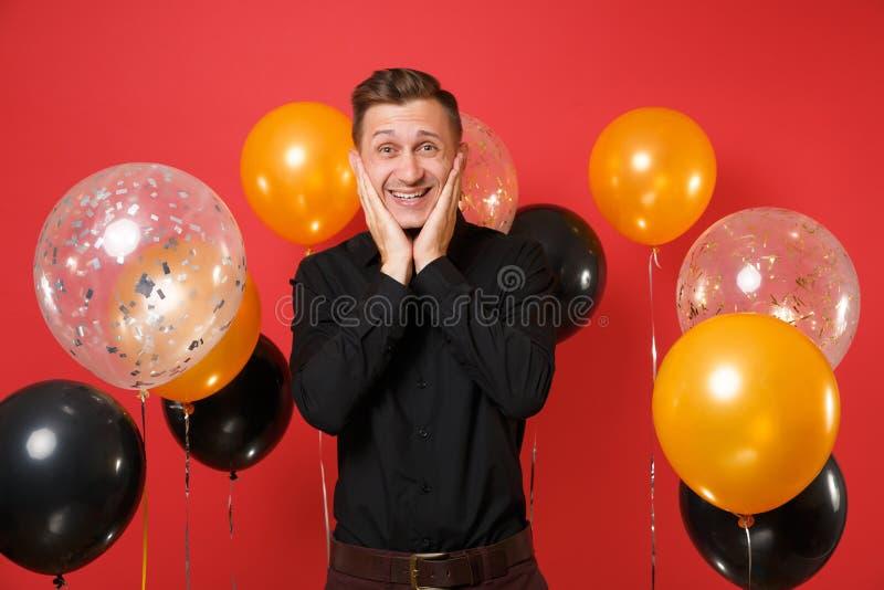 Lächelnder junger Mann im schwarzen klassischen Hemd, das Hände auf Gesicht auf hellen roten Hintergrundluftballonen hält St.-Val lizenzfreie stockfotografie